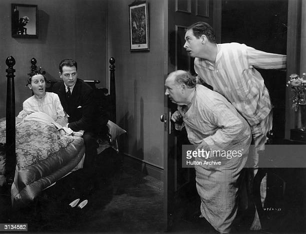 Reginald Denny caught in a compromising situation by William Austin in striped pyjamas in a scene from the film 'Embarrassing Moments' directed by...