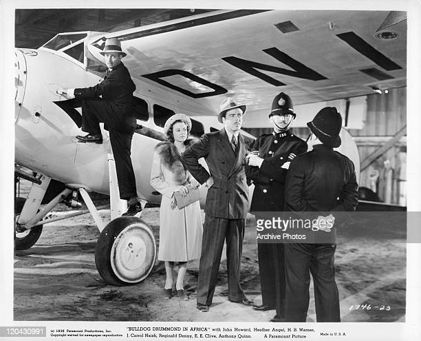 Reginald Denny climbs up a plane while Heather Angel and John Howard talk with the police in a scene from the film 'Bulldog Drummond in Africa' 1938