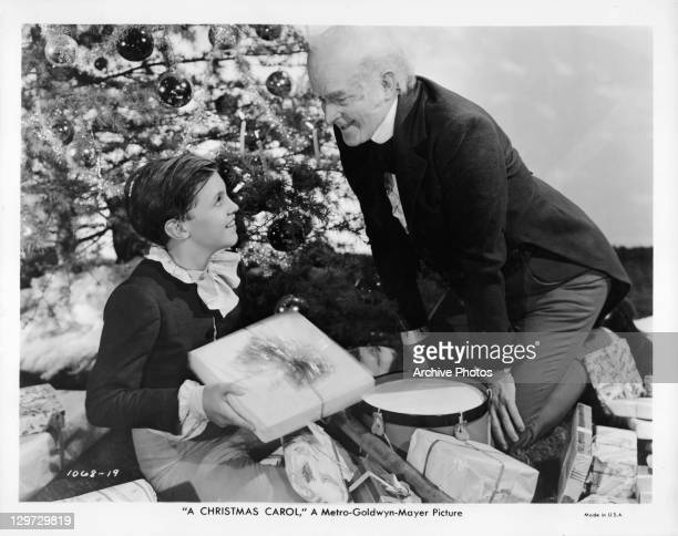 Reginald Owen giving a gift to child actor Terry Kilburn next to a Christmas tree in a scene from the film 'A Christmas Carol' 1938
