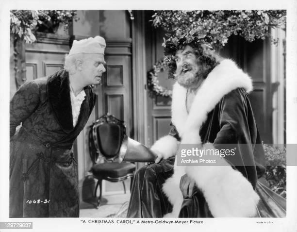 Reginald Owen listening to Lionel Braham leading into the snow in a scene from the film 'A Christmas Carol' 1938