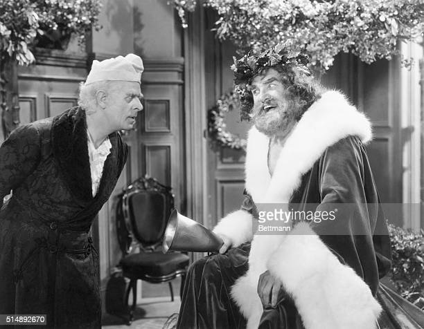 Reginald Owen playing Scrooge confronts the Ghost of Christmas Present played by Lionel Braham in the 1938 MGM production of A Christmas Carol...