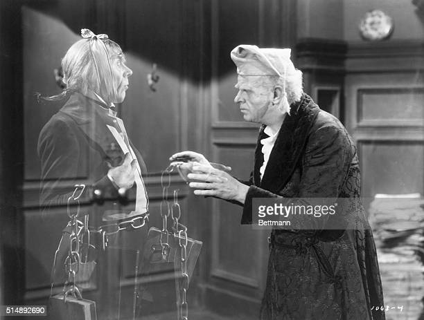 Reginald Owen playing Scrooge speaks with his dead business partner Marley played by Leo G Carroll during the 1938 MGM production of A Christmas...