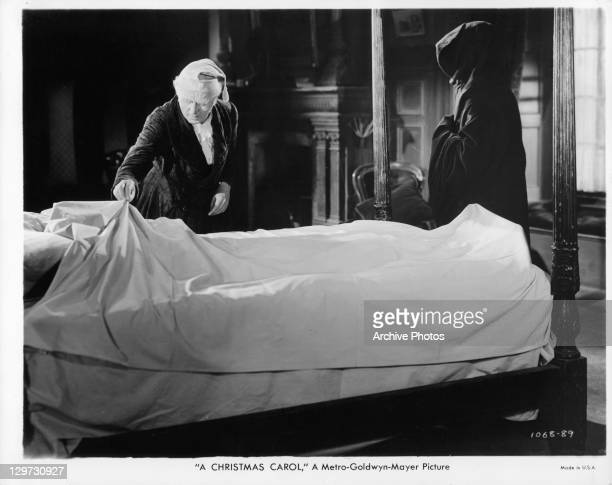 Reginald Owen pulling sheet back on bed as D'Arcy Corrigan watches in a scene from the film 'A Christmas Carol' 1938