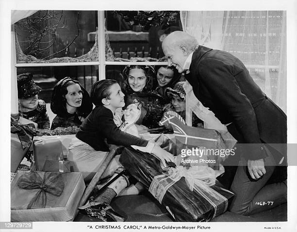 Reginald Owen smiling after giving present to child in a scene from the film 'A Christmas Carol' 1938
