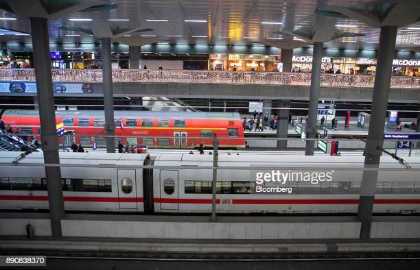 A Regio train operated by Deutsche Bahn AG stands at a platform beyond a Deutsche Bahn InterCity Express train at Berlin Central Station in Berlin...