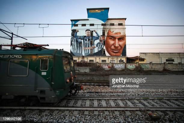 Regioanl train passes by a murales by Sicilian artists Rick & Loste depicting Atalanta BC Head coach Giampiero Gasperini, players Duvan Zapata, Josip...