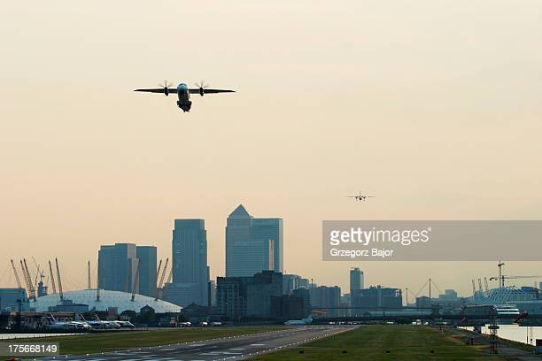 Regional aircraft is taking off while another is approaching the runway at London City Airport, England, UK.