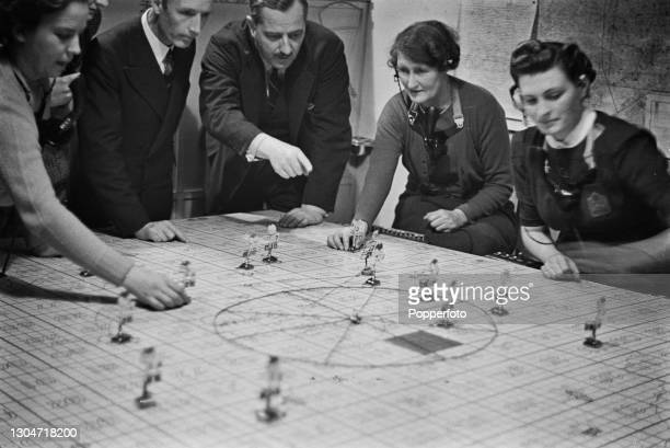 Regional Commissioner The Earl of Dudley, in centre, observes plotters tracking the direction of enemy aircraft in a Midland Region Fire Control room...