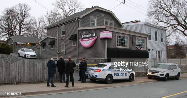 Regional police investigators confer outside the Atlantic Denture Clinic April 20 2020 in Dartmouth Nova Scotia Canada The clinic was owned by the...