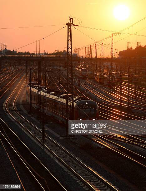A regional train of German railway operator Deutsche Bahn drives near the central railway station during sunset in Munich southern Germany on...