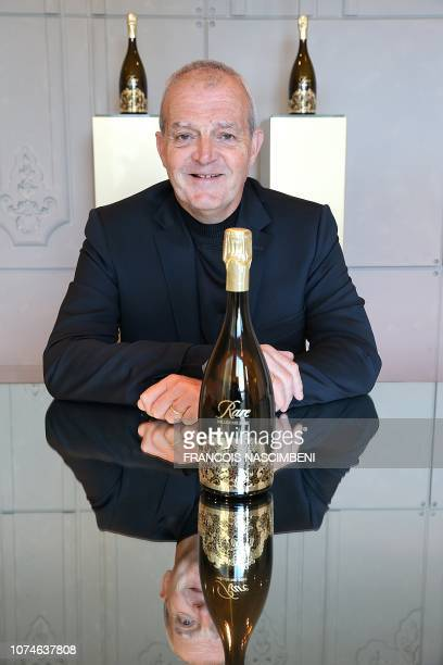 """Regis Camus, former cave chief at Piper-Heidsieck, poses next to a """"Rare Champagne"""" bottle, on September 28, 2018 in Reims."""