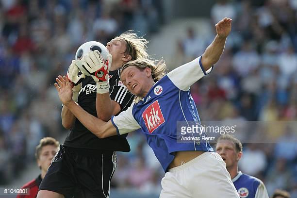 Regis Dorn of Rostock and goalkeeper Rene Adler of Leverkusen battle for the ball during the Bundesliga match between Hansa Rostock and Bayer...