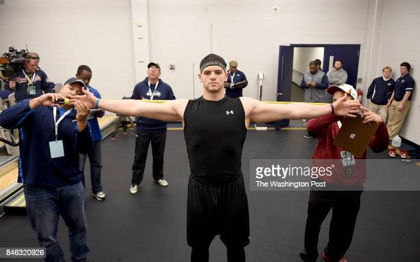 Regis Ellis, college scout for the San Diego Chargers and Jeffrey Scott, scouting assistant for The Washington Redskins measure the wingspan of...