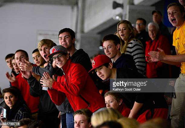 Regis fans clap and wave watching as Resurrection's Zach Lish is escorted from the ice after being ejected from the game The Regis Jesuit High School...