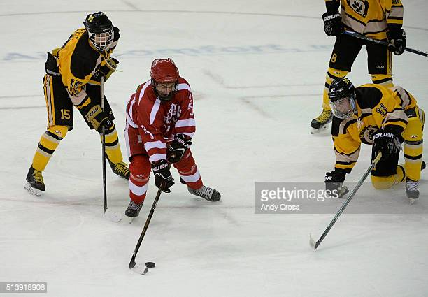 Regis Jesuit forward Jack Kilkenny #16 lines up a shot and scores against Monarch defenders Leo Felt #15 left and Adam Tybor #11 right in the second...