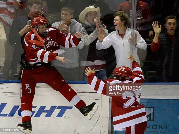 Regis Jesuit hockey players Cale Woodley #21 left and teammate Ian Aylmer #25 right celebrate after defeating the Monarch Coyotes 61 to win the...