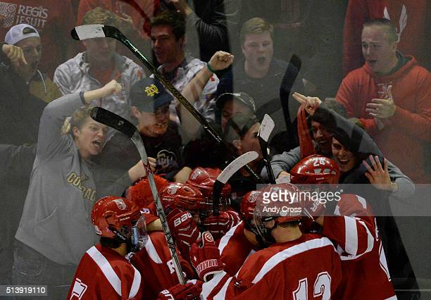 Regis Jesuit teammates swarm forward Jack Kilkenny #16 after he scored against Monarch in the second period during the Colorado State 2016 High...