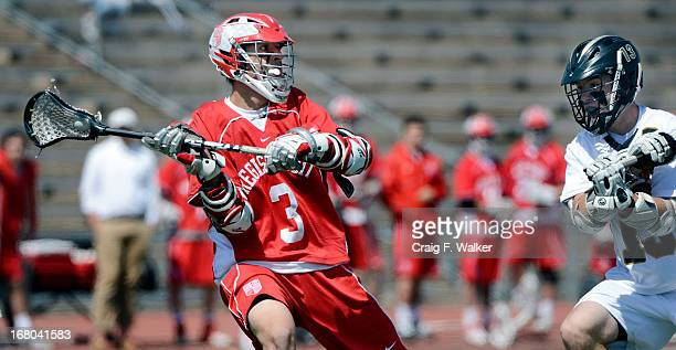 Regis Jesuit's Aaron Horvat is defended by Arapahoe's Kiely O'Connor during the varsity high school lacrosse game between the Arapahoe Warriors and...