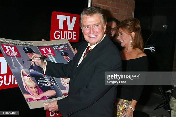 Regis Philbin signs a large poster copy of his TV Guide cover in which he is dressed as Major Nelson from I Dream of Jeannie