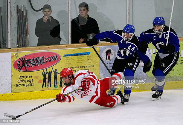 Regis's Andre Dugas falls to the ice with Resurrection's Garrett Devine and Zach Lish in pursuit The Regis Jesuit High School hockey team takes on...