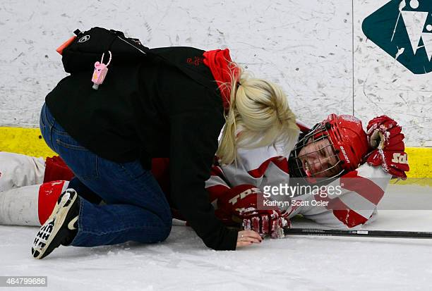 Regis's Cale Woodley stays down on the ice after being injured The Regis Jesuit High School hockey team takes on Resurrection Christian High School...