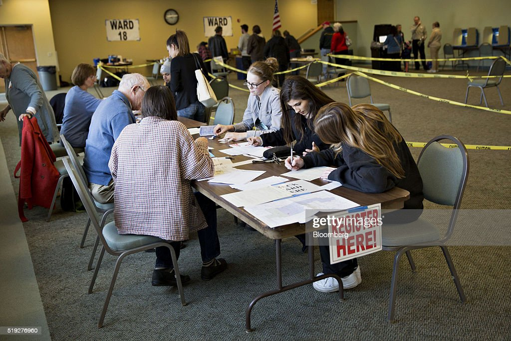 A 'Register Here' sign hangs on a table as residents fill out paperwork at a polling location during the presidential primary vote in Waukesha, Wisconsin, U.S., on Tuesday, April 5, 2016. Wisconsin voters went to the polls Tuesday to decide whether Donald Trump's latest self-inflicted wounds are deep enough to deny him a win in the state's Republican primary, and, in turn, to diminish his hopes of winning the presidential nomination. Photographer: Daniel Acker/Bloomberg via Getty Images