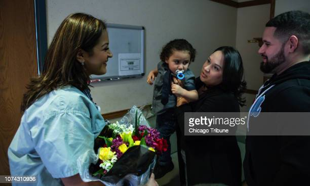 Registered nurse Claudia Lopez left reunites with Jacob Roman center held by his mother Vicelis Negron as his father Alexander Roman looks on Dec 10...