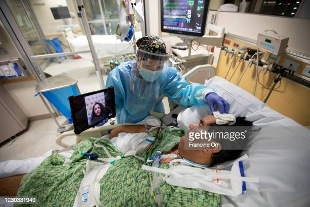 Registered Nurse Kat Yi holds an iPad up to Eduardo Rojas so that his wife Angelica Rojas inside the ICU at Providence St. Jude Medical Center...