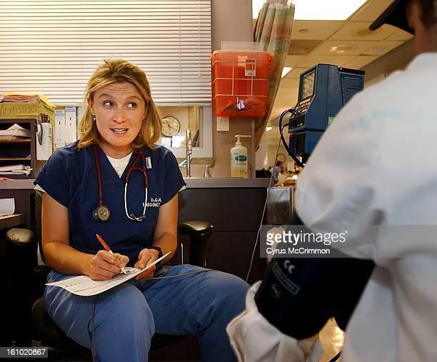 Registered nurse KC Lejameyer delivers a medical screening exam for a walk in patient at Denver Health and Medical Center on Wednesday May 22 2002...