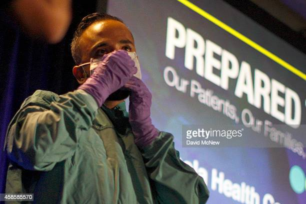 Registered nurse Peter Sidhu demonstrates how to put on and take off personal protective equipment or PPE during an Ebola safety presentation by the...