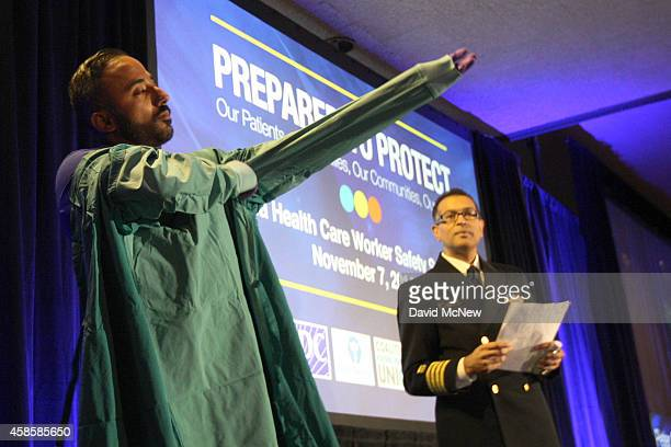 Registered nurse Peter Sidhu demonstrates how to put on and take off personal protective equipment or PPE as Dr Arjun Srinivasan watches during an...