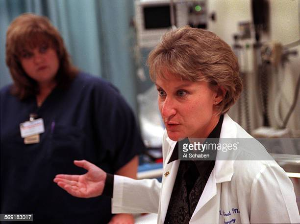 Registered nurse Sherlene Stepp, left, listens to Dr. Marianne Cinat, UCI Medical Center trauma surgeon, speak about providing care to Brandon...