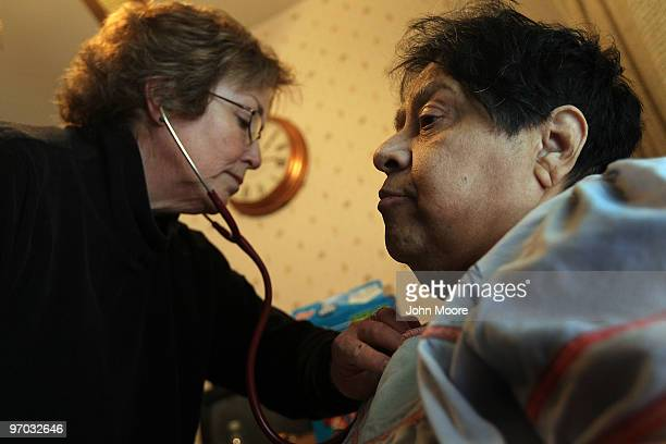 Registered nurse Susan Eager checks the breathing of Jane Awise who suffers from severe diabetes while performing a home health care visit on...