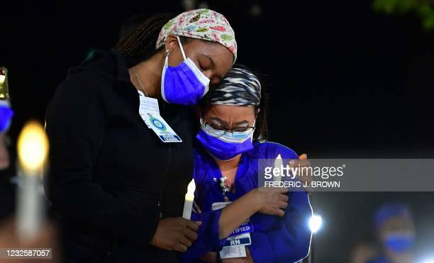 Registered nurses Theresa Austin and Rosell Mahawan grieve and console one another during a candlelight vigil at Kaiser Permanente Hospital in...