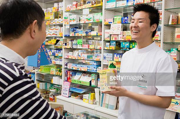 Registered Vendor of Drugstore Showing a Box of Medicine to Customer