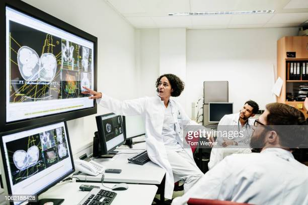 registrar reviewing patient's test results with doctors - medicijnen stockfoto's en -beelden
