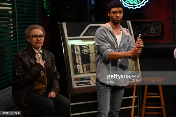 """Regé-Jean Page"""" Episode 1798 -- Pictured: Kate McKinnon and host Regé-Jean Page during the """"Pool Hall"""" sketch on Saturday, February 20, 2021 --"""