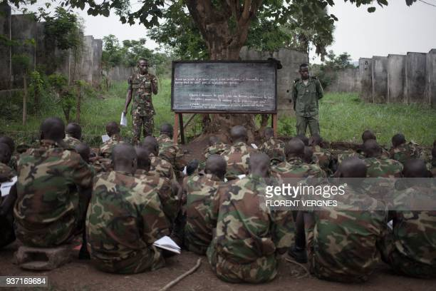 A regular army instructor teaches military tactics at Kassai camp to former militiamen demobilized from armed groups in Bangui on March 14 2018 At...