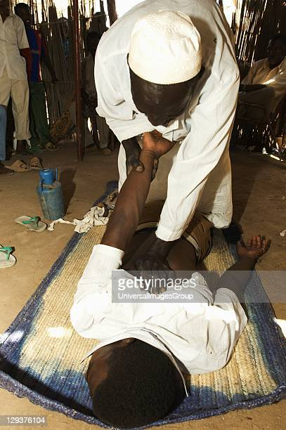 Regular surgery in countryside outside Khartoum countrys capital healer treating patient for back problem While traditional medicine still holds sway...