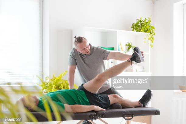 rehab therapist stretching man's legs - izusek stock pictures, royalty-free photos & images