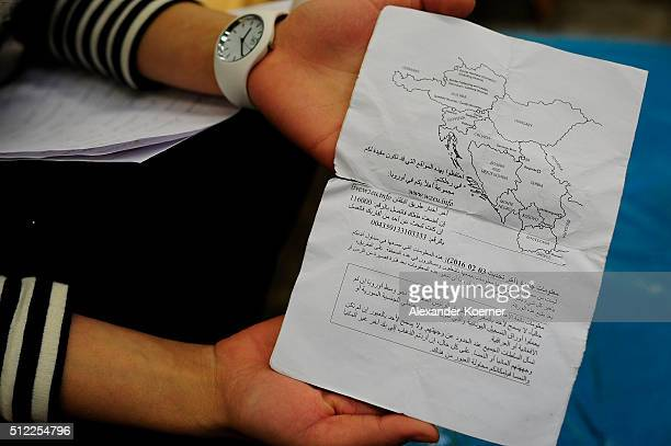 Reham Amairy from Bagdad Iraq shows a guide on how to travel to Germany given by volunteers after arriving at the shores of the Island of Lesbos at a...