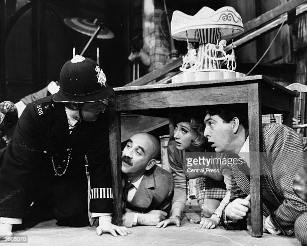 A rehearsal for the comedy 'Everybody Loves Opal' at the Vaudeville Theatre Robert Arnold as a policeman looks under a table at Warren Mitchell Liz...