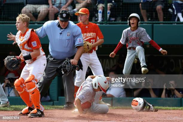 Rei Ichisawa of Japan scores a second inning run in front of catcher Chandler Spencer of the Southwest Team from Texas during the Champioinship Game...