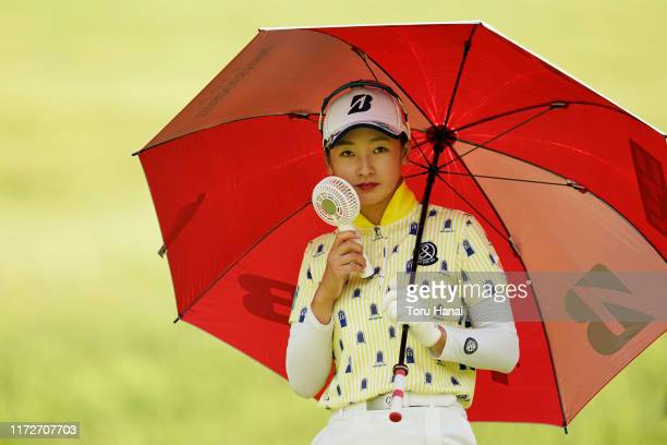 Rei Matsuda of Japan uses a portable fan after her tee shot on the 16th hole during the first round of the Golf5 Ladies Tournament at Golf5 Country...