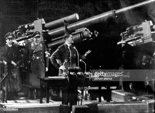 Reich Chancellor Adolf Hitler delivers a speech in front of an antiaircraft gun to the workers of an arms factory To the left Propaganda Minister...