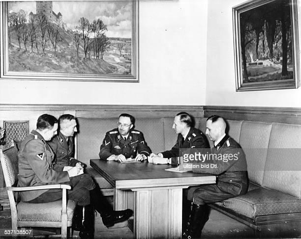 'Reichsführer SS Heinrich Himmler and his colleagues at a meeting. From left: Franz Josef Huber , Arthur Nebe , Heinrich Himmler, Reinhard Heydrich...