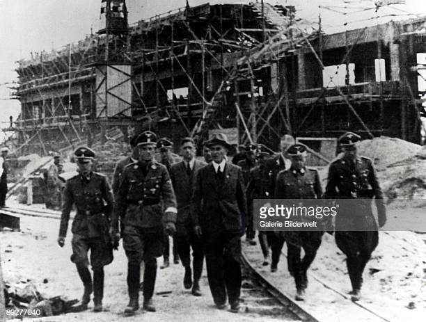 ReichsfuhrerSS Heinrich Himmler carries out an inspection of the MonowitzBuna plant at Auschwitz Poland 17th18th July 1942 From left to right SS...