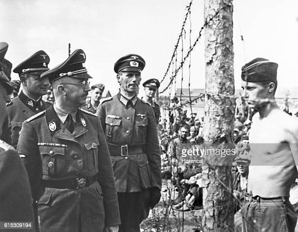 ReichsfuhrerSS Himmler takes a look through a barbedwire fence to inspect Russian prisoners of war ca 1940s | Location prisoner of war camp