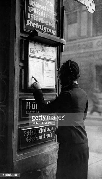 Reichssender series Woman is reading the menu of the 'EgererBierstuben' at the entrance of the Reichssender Leipzig Photographer Ullmann Published by...