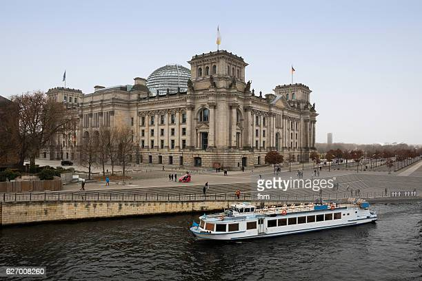 Reichstag building/ german parliament building with tourist sightseeing boat (Berlin Mitte/ Germany)
